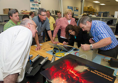 At right, Mark Christl demonstrates the spectrometer to representatives from the Johnson Space Center and Marshall. From left are Nasser Barghouty from Marshall, Edward Semones from Johnson, Chris Cianciola from Marshall, and Catherine McLeod and Bobbie Swan from Johnson.