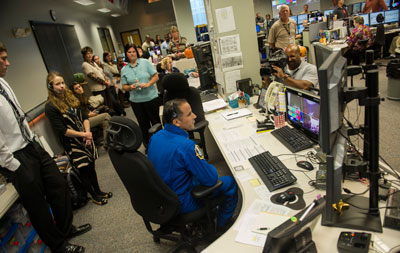 Astronaut Joe Acaba, center, who lived and worked nearly four months as a flight engineer aboard the International Space Station, talks with current station astronauts from a console in the Marshall Space Flight Center's Payload Operations Center.