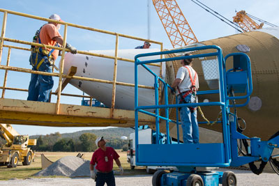 Center operations personnel add a nose cone to the space shuttle solid rocket booster added to the propulsion park display outside Marshall's Building 4205, the Propulsion Research & Development Laboratory.