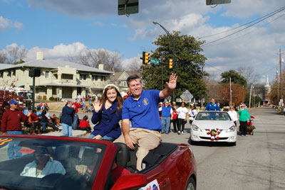 Marshall Space Flight Center Director Patrick Scheuermann, right, and his daughter, Christina, wave to people lined up along the streets of downtown Huntsville Dec. 1 for the WAAY 31 Christmas Parade. Accompanying Scheuermann is his wife, Sarah, in the front passenger seat.