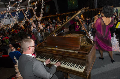 NASA Marshall Space Flight Center team members are entertained by pianist Christopher-Joel Carter, left, and vocalist Jennifer Simmons, a Marshall education program specialist, right, at the center's holiday reception Dec. 13 in the Activities Building 4316.
