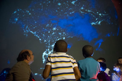 Dr. Bill Cooke, left, lead of Marshall's Meteoroid Environments Office, takes 'snoozeum' participants on a twinkling tour of the United States via an inflatable planetarium.