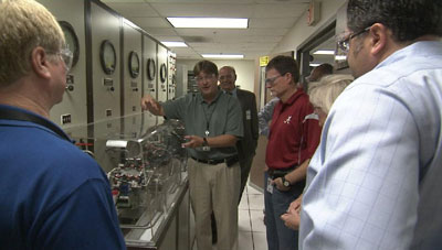 During a recent tour for Space Launch System Program managers, Mike Kynard, left, manager of the program's Engines element office, explains how test personnel use working parts from an RS-25 engine to test the new engine control unit at the Marshall Center test facilities.