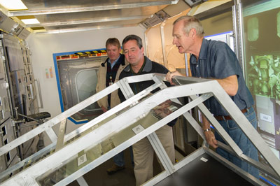 Gordy Seuell, right -- an engineer with Teledyne Brown Engineering Inc., supporting Marshall's Engineering Directorate -- demonstrates how the space station rack mock-up rotates to Jay Onken, center, manager of the Mission Operations Laboratory, and Tony Cox, operations lead for Teledyne Brown.