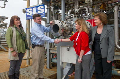 Pictured from left to right in front of the F-1 gas generator are: Dynetics Program Manager Kim Doering, Dynetics Deputy Program Manager Andy Crocker, Marshall Partnerships Manager Stacy Counts, and Marshall Project Manager for Dynetics Whitney Young.