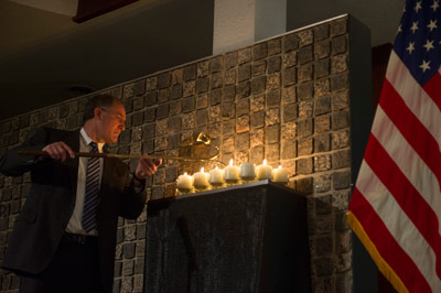 Steve Cash, director of Marshall's Safety & Mission Assurance Directorate, lights candles while Marshall Center Deputy Director Teresa Vanhooser, not pictured, reads the names of each of the 17 fallen astronauts.
