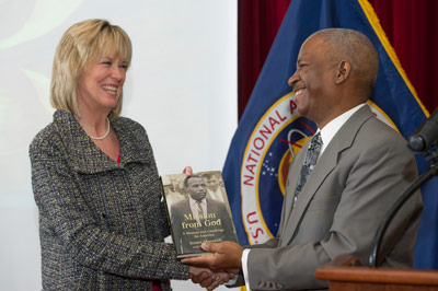 John Meredith, right, presents the book, 'A Mission from God: A Memoir and Challenge for America' -- written by his father, civil rights activist James Meredith -- to Marshall Center Deputy Director Teresa Vanhooser, as a gift for the Marshall Center library.