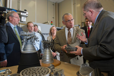 During his Feb. 22 visit to the National Center for Advanced Manufacturing Rapid Prototyping Facility at NASA's Marshall Space Flight Center, NASA Administrator Charles Bolden, center, talks with Frank Ledbetter, right, about the use of 3-D printing and prototyping technology to create parts.