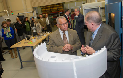 NASA Administrator Charles Bolden, left, talks with Frank Ledbetter about a part of a prototype for the core stage-to-booster attach fitting during Bolden's Feb. 22 visit to the National Center for Advanced Manufacturing Rapid Prototyping Facility at Marshall.
