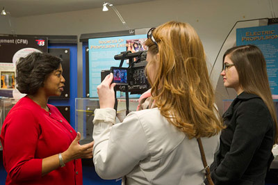 Tawnya Laughinghouse, left, assistant branch chief of the Marshall Engineering Environmental Effects Branch, discusses her work with Butler High School junior Caroline Hernandez, right, while being filmed by WAAY TV reporter Lillian Askins.