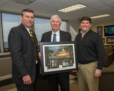 NASA's Marshall Space Flight Center Director Patrick Scheuermann, left, presents U.S. Rep. Mo Brooks of Alabama's 5th Congressional District, center, with a photo collage from the F-1 Gas Generator test firing which he attended Jan. 24.