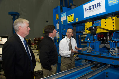 U.S. Rep. Mo Brooks of Alabama's 5th District, left, and U.S. Rep. Steven Palazzo of Mississippi's 4th District, center, listen as David Beaman, right, manager of the Space Launch System Spacecraft & Payload Integration Office at the Marshall Center, explains the process of friction stir welding.
