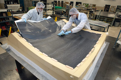 Langley engineers work on the diaphragm pathfinder for the stage adapter. The diaphragm is a contamination barrier, which keeps the gases from the launch vehicle away from the spacecraft.