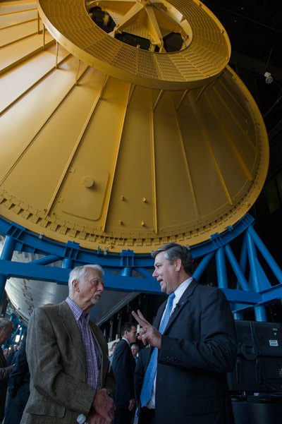 Marshall Center Director Patrick Scheuermann, right, talks with former astronaut Owen Garriott beneath the Saturn V rocket suspended in the Davidson Center for Space Exploration at the U.S. Space & Rocket Center.