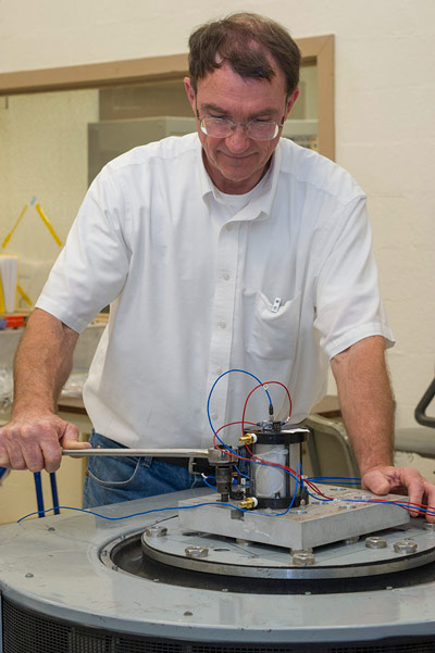 Rocky Stephens, test engineer in the Test Laboratory Structural Dynamics Test Branch, fastens a candidate actuator to an electromagnetic shaker for random vibration testing during the Launch Abort System Ogive hatch actuator testing that recently occurred at Marshall.