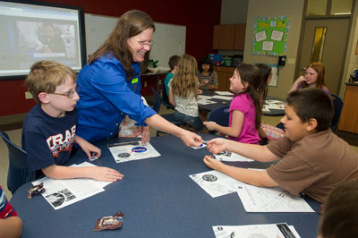 Using a fun hands-on activity last month, Carol Jacobs, a payload operations director at Marshall, teaches students at Blossomwood Elementary School in Huntsville about science aboard the International Space Station.