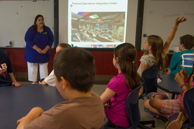 A Blossomwood Elementary School student eagerly raises her hand to ask a question during a presentation by Payload Operations Manager Pat Patterson about how science conducted aboard the International Space Station is leading to benefits for people on Earth.