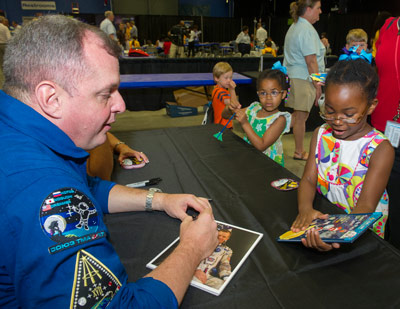 NASA astronaut T.J. Creamer, left, a payload operations director in the Marshall Space Flight Center's Payload Operations Integration Center, signs his official NASA portrait for visitors during