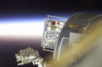 Photo description: Backdropped by a sunrise, the newly installed Materials International Space Station Experiment (MISSE) is visible on the International Space Station.