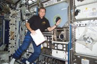 Photo description: Expedition Five flight engineer Peggy Whitson is shown with the Microgravity Science Glovebox following its installation in the Destiny Laboratory module.