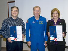 Astronaut Dominic Gorie (center) stands with Silver Snoopy recipients Mounir Sabbagh and Marsha Lynn Ladner.