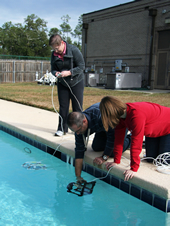 An employee of the Naval Research Laboratory at NASA's John C. Stennis Space Center, helps  teachers deploy a remotely-operated underwater Sea Perch robot.