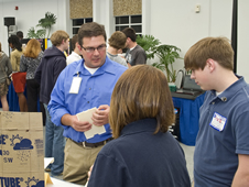 An aerospace engineer at Stennis Space Center talks with students from East Central High School in Hurley, Miss., during a HUNCH showcase event at Stennis.