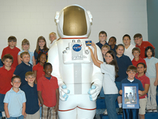 Students at South Hancock Elementary School gather around Orbie the Astronaut as the teacher affixes a nameplate to the Stennis Space Center mascot.