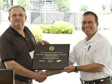 SSC Deputy Director Rick Gilbrech (right) accepts a plaque designating the rocket engine test facility as a VPP Star site, a designation of safety excellence.