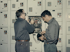 Global Associates employee Andy Anderson (l) and a colleague make repairs to a motor control center at the Mississippi Test Facility (now John C. Stennis Space Center) in 1971.