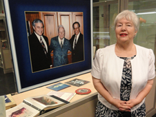 Wealtha Fortune Weaver stands next to a photo of her father, Capt. William C. Fortune (center) the first site manager of the Mississippi Test Operations.