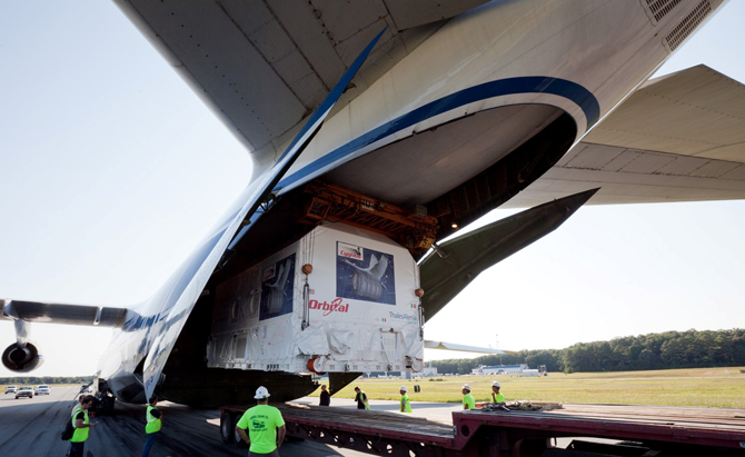 Workers unload the Cygnus payload from a cargo plane at Wallops