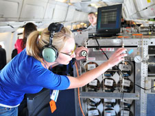 Esther Thomas, a University of New Orleans graduate student, operates the Whole Air Sampler instrument aboard NASA's DC-8 flying laboratory during the 2010 Student Airborne Research Program.