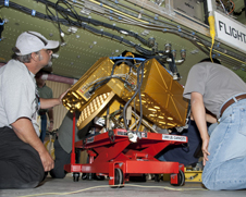 two men adjust a golden instrument package under a fuselage