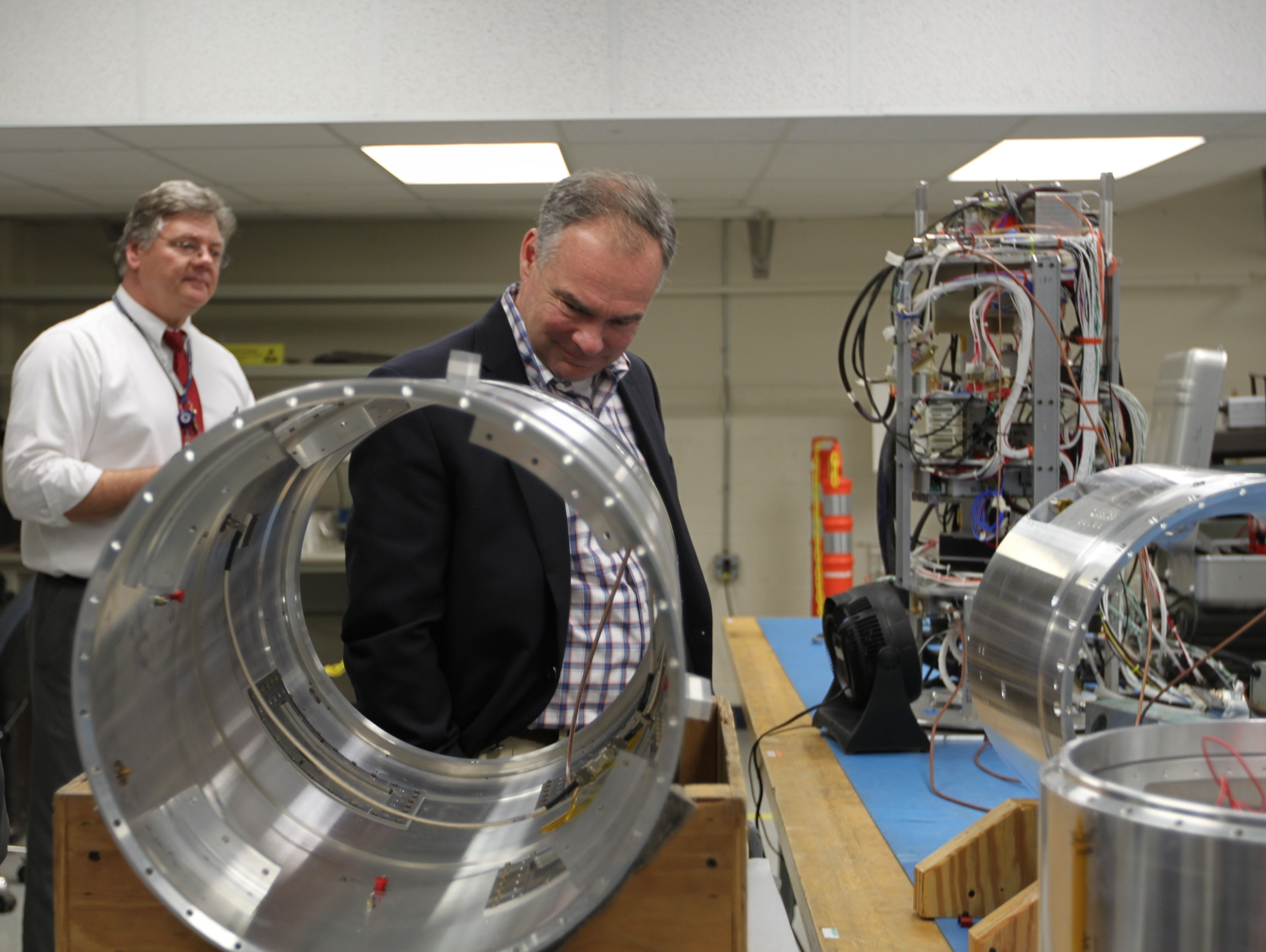 Virginia Senator Tim Kaine studies a payload skin section of a sounding rocket at Wallops Flight Facility.