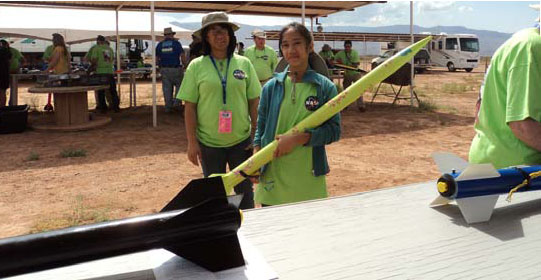 A junior rocket student waits for her rocket to be certified.
