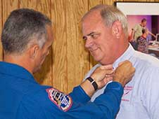 In August 2007, NASA Astronaut Danny Olivas pins the Silver Snoopy on Mitchell. The Silver Snoopy Award is the Astronaut Office's highest and only award. (wstf0807e05750).