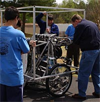 Students watch as NASA engineers measure dimensions of moonbuggy