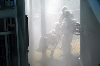 The pad's fire suppression system showers the rescuers during the pad disaster simulation.