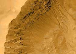 Channels in a Martian  crater, in an image taken in 2000 by the Mars Global Surveyor, suggest  to scientists that liquid water may have flowed across the surface of  Mars in recent times.