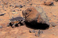 The Sojourner Rover examines a rock on Mars. The rover traveled from Earth aboard the Mars Pathfinder space probe, then rolled down a ramp to the surface. Sojourner is only 24 3/4 inches (63 centimeters) long.