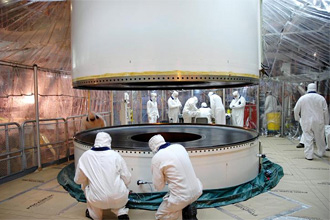 Technicians work to assemble two booster segments