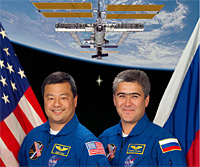 Leroy Chiao and Salizhan Sharipov with an image of the International Space Station behind them