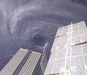This image features the eye of Hurricane Ivan at center, partially framed by solar array panels on the International Space Station.