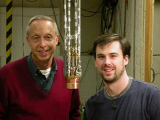 researchers stand in front of hte cryostat insert, where the liquid helium was cooled