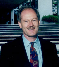 This picture shows a sandy-haired Chris Webster grinning for the camera, sporting a black suit, light blue dress shirt with a nice tie, a gently receding hairline, and a moustache as wide as the top of his upper lip.