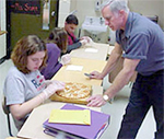 A visually impaired student is tracing a pizza with her hands