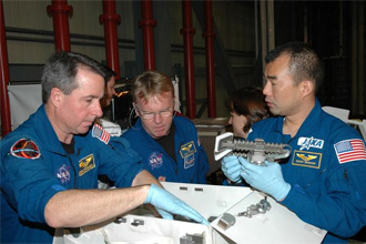 Astronauts look at tools to be used on STS-114
