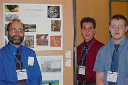 Teacher Mr. Moore stands to the left of a student poster project showing various satellite images of different locations as two students stand to the right of the project