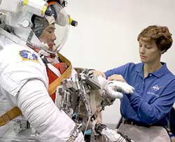 STS-114 Commander Eileen Collins, right, assists Mission Specialist Soichi Noguchi